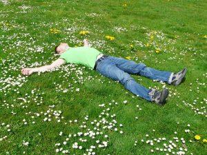 野原で大の字で寝る男性