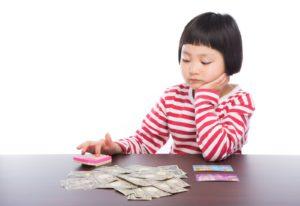 電卓でお金の計算をする女の子
